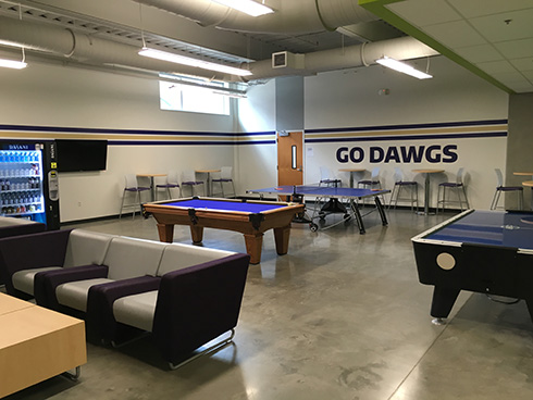 Photo of UWY Game Room showing TVs, pool table, ping-pong table, couches.