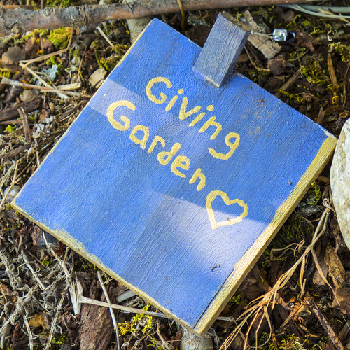 A painted tile that have Giving Garden Written on it as well as a heart.