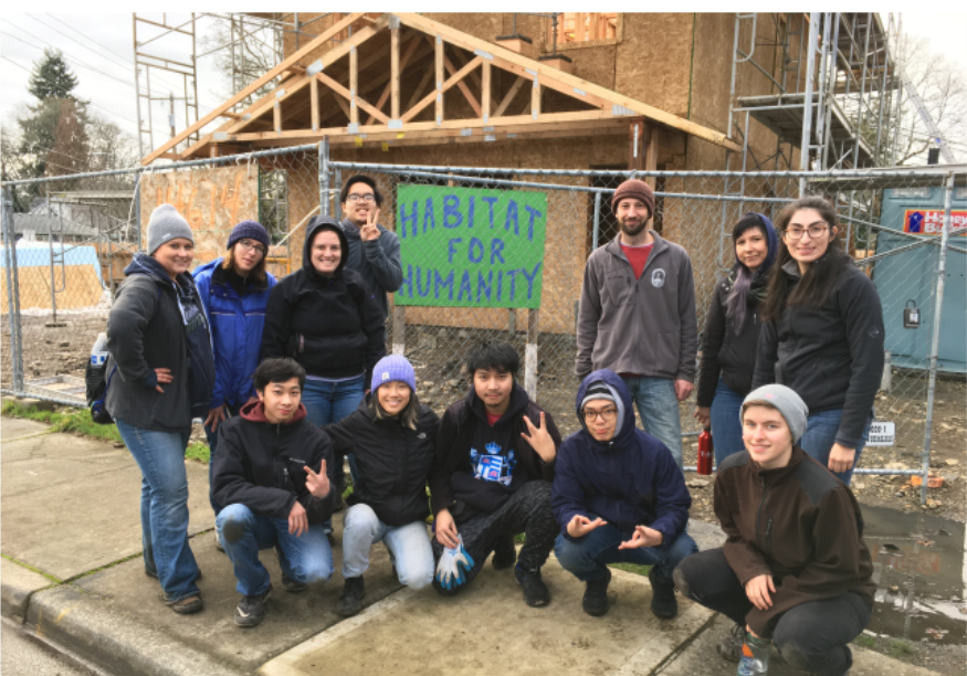 A group of UWT volunteers in front of a Habitat for Humanity sign and the house they worked on as their service project.