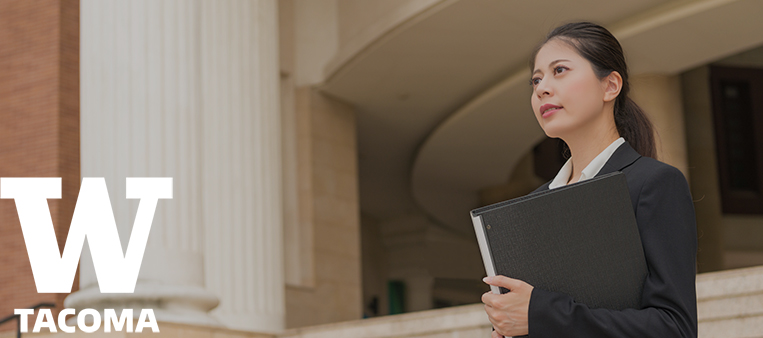 Woman standing in front of building with binder