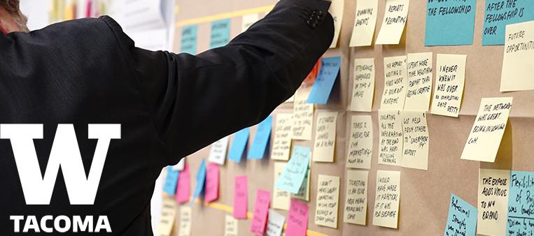 Man placing sticky note on cork board