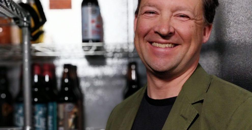 White man smiling, next to bottles of beer
