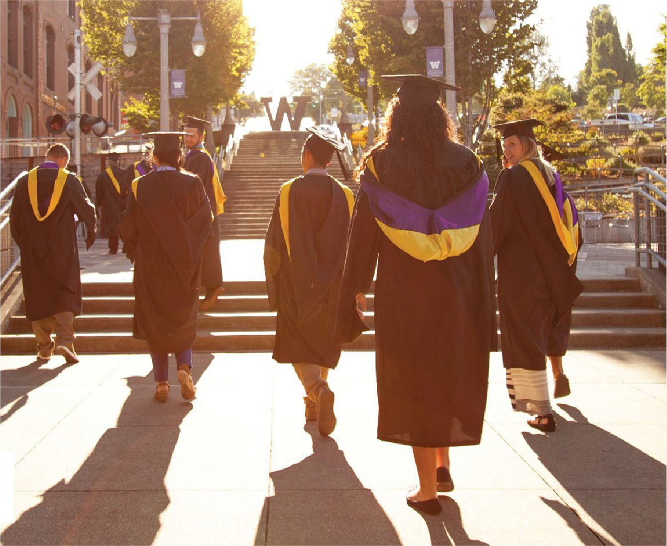 several graduating students walking up the stairs towards the W sign on the UW Tacoma campus
