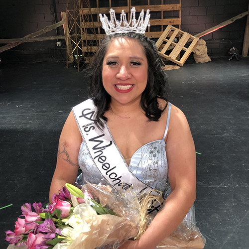Erica Myron, wearing tiara and sash, carrying flower bouquet, shortly after being named Ms. Wheelchair USA.