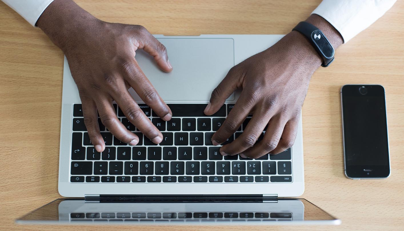 Dark-skinned hands typing on a laptop