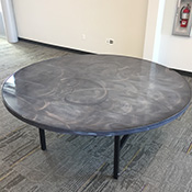 Round table with silver and black swirled surface top and black legs