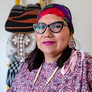Headshot of UW Tacoma Ed.D. Director Robin Minthorn. Minthorn is wearing glasses, a multicolored headwrap and a floral print dress.