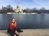 person sitting near water with the US Capitol in the background
